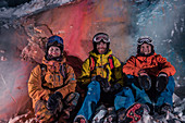 Group portrait of three winter athletes with color powder, Pitztal, Austria,