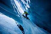 Snowboarder rides in an ice cave, Pitztal, Austria,