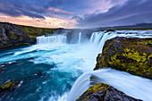 Die türkis-weiß leuchtende Gischt des Wasserfalls Godafoss bei Sonnenuntergang, Island, Europa