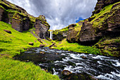 Rocky landscape around Kvernufoss waterfall with river in foreground: Iceland, Europe