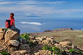 Frau beim Wandern sitzt auf Fels und blickt auf El Hierro, am Fortaleza, La Gomera, Kanarische Inseln, Kanaren, Spanien