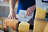 Käsehändler, der Ziegenkäse einwickelt