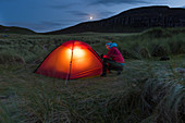 A woman in front of lit tent, Sandwood Bay, Highlands, Scotland, UK