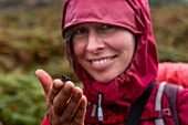 A female wanderer holds a small frog on her fingers, Inverpolly Nature Reserve, Highlands, Scotland, UK