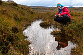A female walker on a bog, Inverpolly Nature Reserve, Highlands, Scotland, UK
