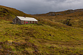 A hiker at Suileag Bothy, Inverpolly Nature Reserve, Highlands, Scotland, UK