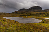 A hiker under the Suilven, Inverpolly Nature Reserve, Highlands, Scotland, UK