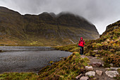 A female walker on the shore of a small lake below the Suilven, Inverpolly Nature Reserve, Highlands, Scotland, UK