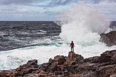 A woman faces the surf of the sea at Sheigra, Highlands, Scotland, United Kingdom