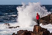 Eine Frau steht auf einem Felsen vor den brechenden Wellen der Brandung bei Sheigra, Highlands, Schottland, Großbritannien