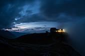 Hell erleuchtete Fenster des Watzmannhaus in der Abenddämmerung, Berchtesgadener Alpen, Berchtesgaden, Deutschland