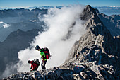 Climbers on the transition to the southern tip of the Watzmann, clouds at the rock, Berchtesgaden Alps, Berchtesgaden, Germany