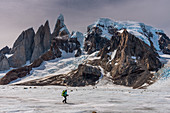 Mountaineer on ice surface in front of Circo de los Altares looks out over Cerro Torre,, Los Glaciares National Park, Patagonia, Argentina