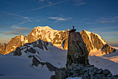 Mountaineer on exposed rock, climb to Aiguille Rochefort, sunrise at Mont Blanc in the background, Mont Blanc group, Chamonix, France