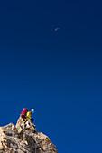 Bergsteiger am Fels vor blauem Himmel, Grat am Dome de Rochefort, Grandes Jorasses, Mont Blanc-Gruppe, Frankreich