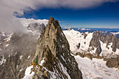 Mountaineer on the ridge of the Grandes Jorasses, in the background Glacier and Aiguilles du Midi, Mont Blanc group, France
