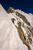 Climber in rock climbing at the Grandes Jorasses, wet snow on the rock, Mont Blanc group, France