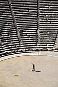 WOMAN STANDS IN ANCIENT THEATER OF EPIDAURUS, ARGOLIS, PELOPONNESE, GREECE
