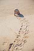 Little child plays on the sandy beach of northern Spain