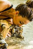 Eine Frau küsst Tigerjunges