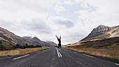Eine Frau springend auf einer Landstraße in Island