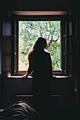 A girl looking out from a window in a farmhouse near Montefollonico, Siena Province, Tuscany, Italy.