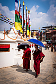 Two monks walking around the Boudhanath Stupa, the Nepal's largest and most important Buddhist monument, Kathmandu, Nepal, Nepalese, Asia, Asian, Himalayan Country, Himalayas.