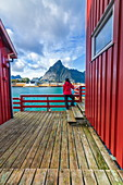 Woman on wooden deck look towards Sakrisoy and Olstinden mountain, Reine, Nordland, Lofoten Islands, Norway