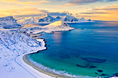 Aerial view of turquoise sea around Haukland beach covered with snow, Vestvagoy, Nordland, Lofoten Islands, Norway