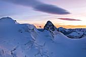 Helicopter in flight on snowy peak of Cresta Guzza towards Piz Bernina, Valmalenco, Lombardy, border of Italy and Switzerland