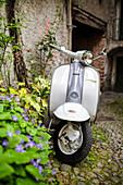 White and grey Lambretta Innocenti scooter in a courtyard, Morbegno, province of Sondrio, Valtellina, Lombardy, Italy