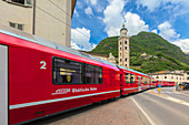 Bernina Express train next to historic Sanctuary of Madonna di Tirano, Sondrio province, Valtellina, Lombardy, Italy