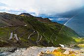 Rainbow on hairpin bends of winding road at Stelvio Pass, South Tyrol side, Valtellina, Lombardy, Italy