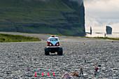 Scale models of vintage camper and figurines on asphalt road, Eysturoy island, Faroe Islands, Denmark