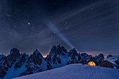 Mount Campedelle, Misurina, Auronzo di Cadore, province of Belluno, Veneto, Italy, Europe. A mountaineer admires the starry sky over the Cadini mountains