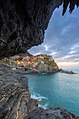 Sunrise on the village of Manarola from a sea cave. Cinque Terre, Liguria, Italy, Europe.