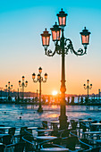 St Mark's square, Venice, Veneto, Italy. Tourists admiring the sunrise over St. Mark's waterfront.