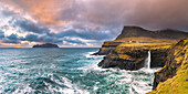 Gasadalur, the iconic waterfall of M?lafossur jumps down from the cliff into the ocean at sunset (Vagar Island, Faroe Islands, Denmark)