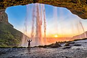 Ein Mädchen hinter dem Wasserfall Seljalandsfoss bei Sonnenuntergang (Skogar, Region Süd, Island, Europa)