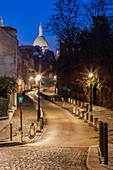 A small street in Montmatre at night with illuminated Sacre Coeur Basilica in the background. Paris, France