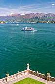 Touristic ferry on Lake Como viewed from Villa del Balbianello gardens on Punta di Lavedo, Lenno, Como province, Lombardy, italy