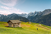 Hiker admiring from an alpine hut the snowy peaks in the background, Tombal, Soglio, Bregaglia Valley, canton of Graub?nden, Switzerland, Europe