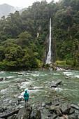 Tourist under the rain admiring Thunder Creek Falls. Mount Aspiring National Park, West Coast region, South Island, New Zealand.