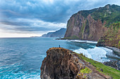Person on a cliff watching the sunrise. Faial, Santana municipality, Madeira region, Portugal.