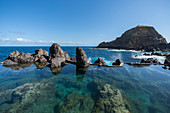 Natural pools with Mole islet in the background. Porto Moniz, Madeira region, Portugal.