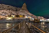The iconic Hammmarskaftet mountain in Reine village, whit Aurora borealis, Lofoten Islands, Northern Norway, Europe