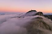 aerial view of La Nuda Mountain at sunset with fog, Cerreto Laghi, municipality of Ventasso, Reggio Emilia province, Emilia Romagna distict, Italy, Europe