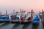 Some traditional venetian gondolas moored at Riva degli Schiavoni with St. George's church on the background, Venice, Veneto, Italy