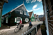 Cyclists and typical houses in Kerkbuurt, Marche island, North Holland, Netherlands