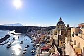 Blick im Gegenlicht auf den kleinen Hafen von Corricella auf der Insel Procida. Im Hintergrund die Insel Ischia, Kampanien, Italien